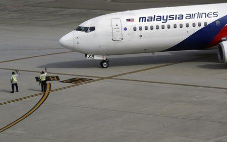 Ground staff wave to a Malaysian Airlines aircraft as it leaves Kuala Lumpur International airport in Sepang outside Kuala Lumpur