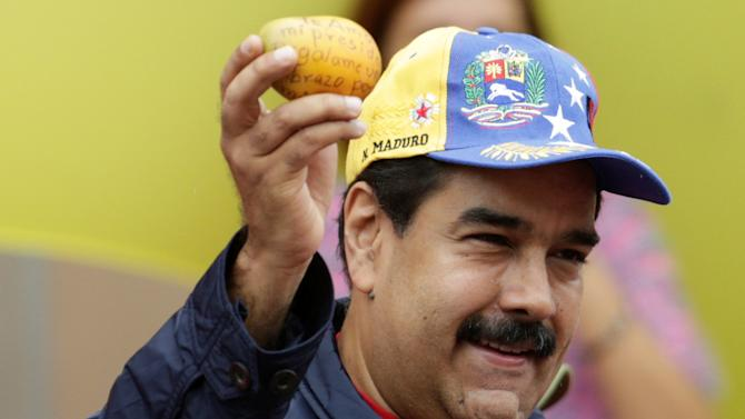 Venezuela's President Nicolas Maduro holds a mango with a message from a supporter during a rally to commemorate May Day, in Caracas