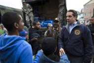 New York Governor Andrew Cuomo greets residents of the Far Rockaways section of the Queens borough of New York, Saturday, Nov. 10, 2012. Despite power returning to many neighborhoods in the metropolitan area, residents of the Far Rockaways continue to live without power and heat due to damage caused by Superstorm Sandy.(AP Photo/John Minchillo)