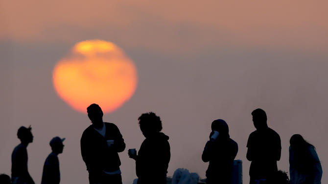 Beach goers stand around a fire pit on, Sunday, April 28, 2013 in Huntington Beach, Calif. Air quality regulators are considering a proposal to ban beach bonfires in Southern California due to health concerns. (AP Photo/Chris Carlson)