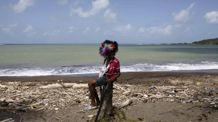 A boy wearing a wig sits on a tree stump during the Congos and Devils ritual celebration in Nombre de Dios