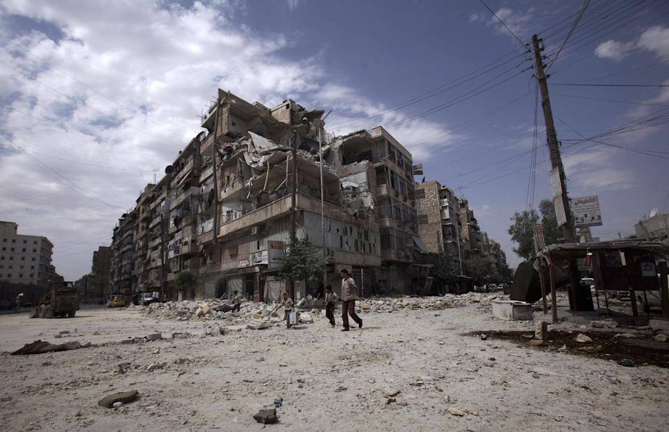 Syrians walk by a building which was damaged by government airstrike in Aleppo, Syria, Tuesday, Sept. 11, 2012. (AP Photo/Muhammed Muheisen)