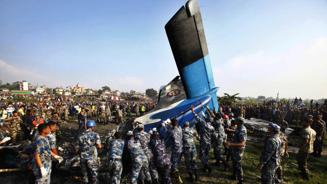 Nepalese police search move the remains of a Sita Air airplane at the crash site near Katmandu, Nepal, early Friday, Sept. 28, 2012.  The plane carrying trekkers into the Everest region crashed just after takeoff Friday morning in Nepal's capital, killing all 19 people on board, authorities said. (AP Photo/Niranjan Shrestha)