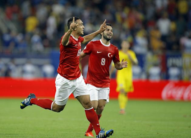 Turkey's Mevlut Erdinc, left, celebrates after scoring his team's second goal during a World Cup Group D qualifying soccer match between Romania and Turkey at the National Arena stadium in Bucharest,