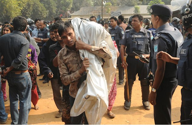 A Bangladeshi man carries the body of his relative killed in a fire at a garment factory outside Dhaka, Bangladesh, Sunday, Nov. 25, 2012. At least 112 people were killed late Saturday night in a fire