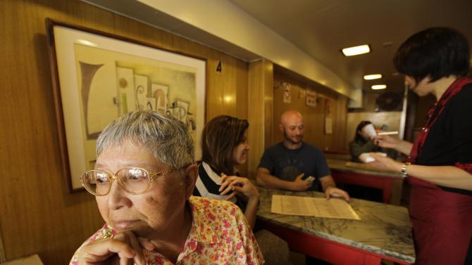 """Darlene Lee, 71, looks out the window after ordering lunch one last time from waitress Fanny He, right, at the Sam Wo restaurant in San Francisco, Friday, April 20, 2012. Lee has been coming to the restaurant for over 60 years since she was a girl growing up in Chinatown. The 100-year-old Chinese restaurant known for having """"the world's rudest waiter"""" is shutting its doors and serving its last customers Friday. (AP Photo/Eric Risberg)"""