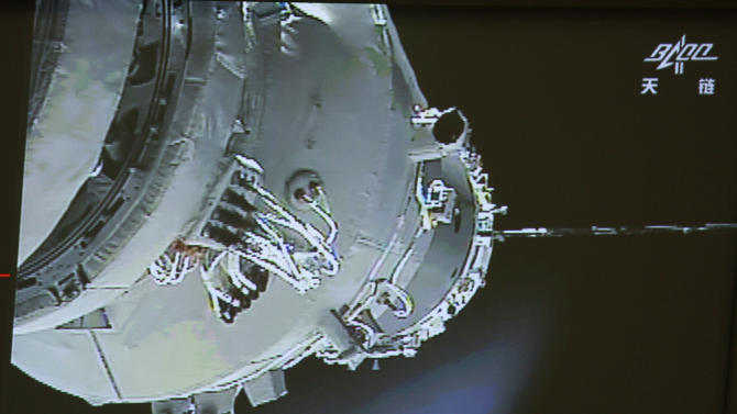In this image made off the screen at the Beijing Aerospace Control Center in Beijing and released by China's Xinhua News Agency, China's Shenzhou-9 manned spacecraft, left, conducts docking with the Tiangong-1 space lab module shortly after 2 p.m. Beijing time (0600 GMT) on Monday, June 18, 2012, 343 kilometers (213 miles) above Earth. (AP Photo/Beijing Aerospace Control Center via Xinhua) NO SALES