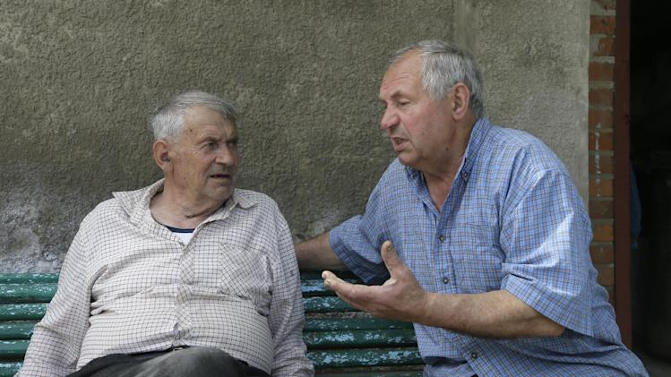 In this picture taken May 10, 2013, Heorhiy Syvyi, 78, left, and Ivan Hrushka share their war memories in their home village of Pidhaitsi close to Ukraine's western city of Lutsk.  Nearly two dozen civilians, primarily women and children, were slaughtered in Pidhaitsi.  Evidence uncovered by AP indicates that Ukrainian Self Defense Legion commander Michael Karkoc's unit was in the area at the time of the massacre. There is no indication any other units were in the area at the time. Heorhiy Syvyi was a 9-year-old boy when troops swarmed into town on Dec. 3 and managed to flee with his father and hide in a shelter covered with branches. His mother and 4-year-old brother were killed.   (AP Photo/Efrem Lukatsky)