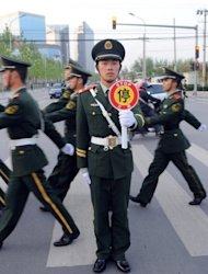 Chinese embassy guards march towards the US embassy compound in Beijing amid unconfirmed reports that blind lawyer Chen Guangcheng is currently at the US embassy