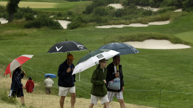 Spectators walk off the course as weather delays the first round of the U.S. Open golf tournament at Merion Golf Club, Thursday, June 13, 2013, in Ardmore, Pa. (AP Photo/Gene J. Puskar)