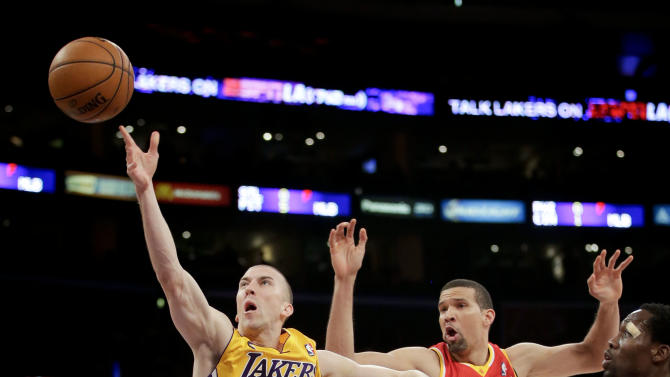 Los Angeles Lakers' Steve Blake, left, shoots against Houston Rockets' Francisco Garcia during the first half of an NBA basketball game in Los Angeles, Wednesday, April 17, 2013. (AP Photo/Jae C. Hong)