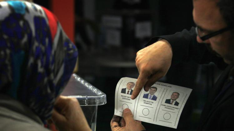 An official shows a member of the Australian Turkish community how to complete a ballot paper as she prepares to vote in Turkey's first direct presidential elections at a polling station in Sydney