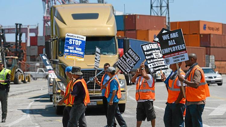 Members of the Teamsters Union picket at LBCT in the Port of Long Beach, Calif., in support of a strike by port truck drivers Tuesday, July 8, 2014. Nearly 1,000 dockworkers briefly walked off their jobs Tuesday at the massive ports of Los Angeles and Long Beach, disrupting the movement of international cargo before a mediator ordered them back. (AP Photo/The Daily Breeze, Stephen Carr)