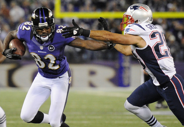 Baltimore Ravens wide receiver Torrey Smith, center, rushes between New England Patriots defenders Dont'a Hightower (54) and Steve Gregory in the second half of an NFL football game in Baltimore, Sund