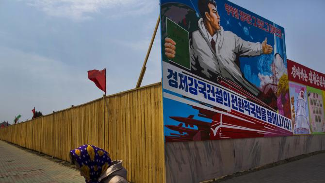 """FILE - In this Saturday, April 13, 2013 file photo, a North Korean woman walks past the outer wall of a construction site where a propaganda billboard depicting the launch of North Korean rockets in Pyongyang, North Korea. Worried that long-seething rifts could escalate over the South China Sea, Southeast Asian leaders are expected this week to press China to agree to start negotiations on a new pact aimed at thwarting a major clash in one of the world's busiest waterways. Concern over North Korea's latest threats is also expected to gain attention over economic issues in the annual summit of the Association of Southeast Asian Nations, or ASEAN, being held Wednesday, April 24 and Thursday, April 25 in Brunei's capital of Bandar Seri Begawan. The billboard reads: """"Lets open up an era to a strong economic country."""" (AP Photo/David Guttenfelder, File)"""