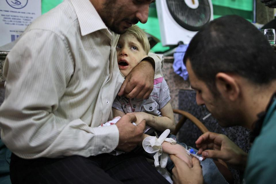 A Syrian child reacts while being treated by a doctor, in a hospital in Aleppo, Syria, Tuesday, Sept. 11, 2012. (AP Photo/Muhammed Muheisen)