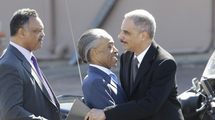 U.S. Attorney General Eric Holder hugs Rev. Al Sharpton in Selma, Ala., Sunday, March 3, 2013. At left is Rev. Jesse Jackson. Holder and Vice President Joe Biden addressed thousands who gathered for the annual Bridge Crossing Jubilee on the 48th anniversary of Bloody Sunday, when Alabama State Troopers beat back marchers when they tried to cross the Edmund Pettus Bridge. (AP Photo/Dave Martin)