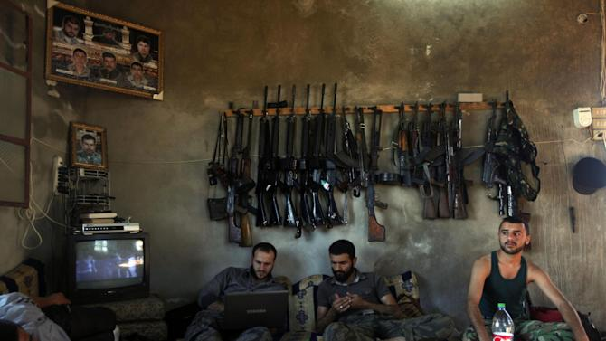 FILE - In this June 12, 2012 file photo, Free Syrian Army fighters sit in a house on the outskirts of Aleppo, Syria. More than 100,000 people have been killed since the start of Syria's conflict over two years ago, an activist group said Wednesday. (AP Photo/Khalil Hamra, File)