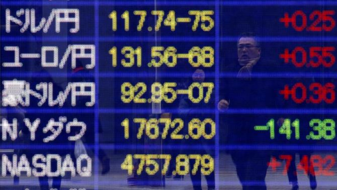 A pedestrian is reflected on an electronic board showing exchange rates and market indices outside a brokerage in Tokyo