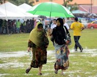 Two Muslim women make their way across a flooded field to listen to opposition leader Anwar Ibrahim speak at a election rally in Ulu Melaka, May 3, 2013. Anwar said only fraud can stop his Malaysian opposition from scoring a historic election win as the rival sides launched a last-ditch campaign blitz Saturday on the eve of a tense vote
