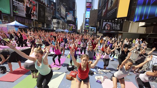 "People practice yoga in New York's Times Square, Friday, June 21, 2013. Yoga enthusiast marked the longest day of the year with five free ""Mind Over Madness"" yoga classes during the11th annual Solstice in Times Square. (AP Photo/Mary Altaffer)"