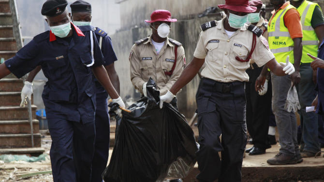 Rescue workers collect bodies at  the site  of a plane crash in Lagos, Nigeria, Monday, June 4, 2012. A passenger plane carrying more than 150 people crashed in Nigeria's largest city on Sunday, government officials said. Firefighters pulled at least one body from a building that was damaged by the crash and searched for survivors as several charred corpses could be seen in the rubble.(AP Photo/Sunday Alamba)