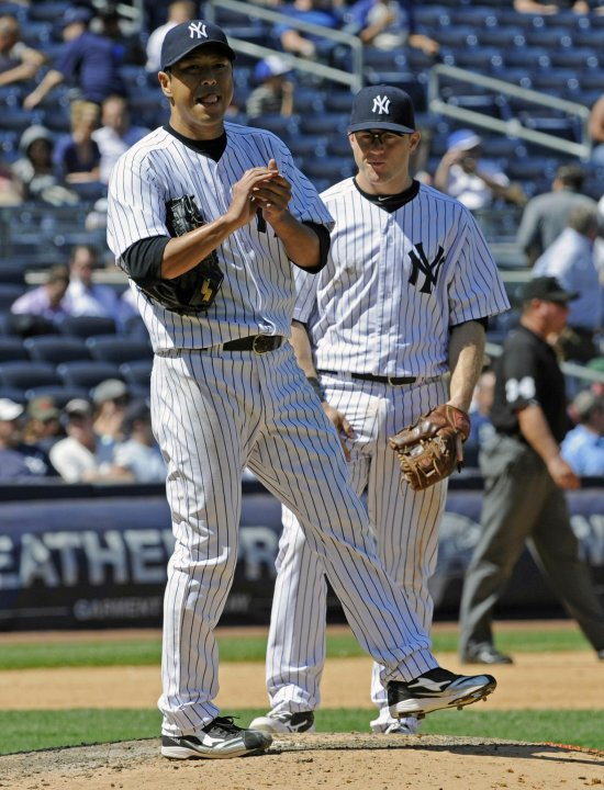 New York Yankees pitcher Hiroki Kuroda reacts as David Adams looks on against the Dodgers in New York