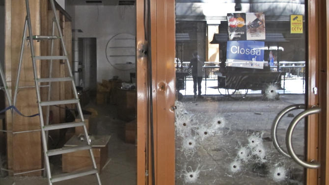 Bullet-holes pepper the glass door of a shop in the Westgate Mall in Nairobi, Kenya Tuesday, Oct. 1, 2013. Kenyan President Uhuru Kenyatta says Kenya will keep its troops in Somalia to help that country's beleaguered government battle the armed Islamic extremist group al-Shabab, which attacked the mall in Nairobi on Sept. 21 claiming at least 67 lives. (AP Photo/Rukmini Callimachi)