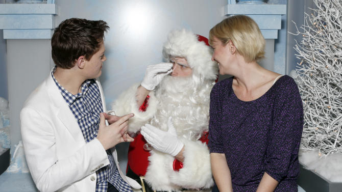 """IMAGE DISTRIBUTED FOR TWENTIETH CENTURY FOX HOME ENTERTAINMENT - Sean Berdy and Amber Zion, right, sign with Santa Claus to celebrate the December 11th Blu-ray, DVD and Digital HD release of ICE AGE: CONTINENTAL DRIFT at the Beverly Center in Los Angeles, on Tuesday, Dec. 6, 2012. Twentieth Century Fox Home Entertainment and Taubman Shopping Centers across the country have partnered to commemorate """"National Signing Santa Day"""" and the industry first Blu-ray special feature with picture-in-picture sign language interpretation.(Photo by Todd Williamson/Invision for Twentieth Century Fox Home Entertainment / AP Images)"""