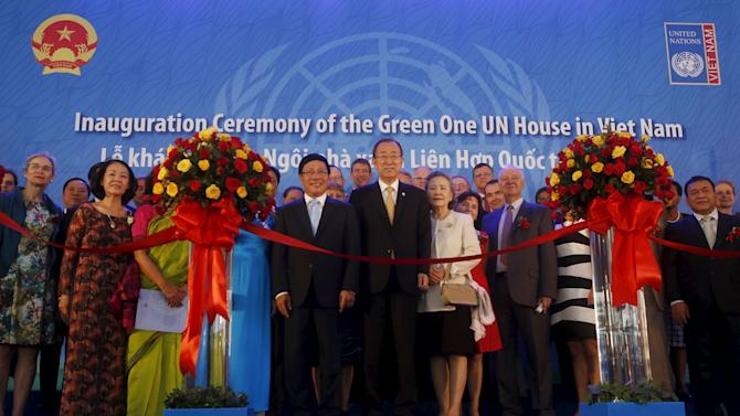 Secretary-General Ban Ki-moon stands next to Pham Binh Minh and Soon-taek as they pose for a photo with UN staff at the inauguration ceremony of the Green One House UN in Hanoi