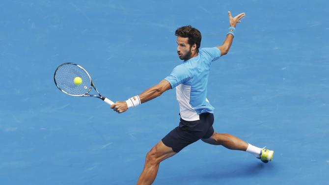 Lopez of Spain hits a shot to Raonic of Canada during their men's singles match at the Australian Open 2015 tennis tournament in Melbourne