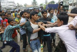Garment workers clash with locals, who they believe are supporting the garment factory owners, during a protest in Dhaka