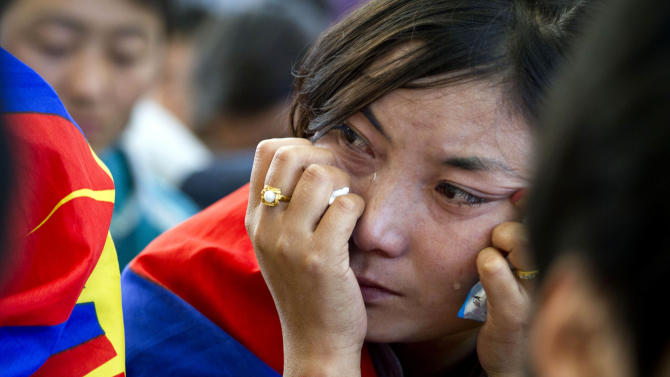 An Tibetan exile cries during a special ceremony to pay homage to 27-year-old Jamphel Yeshi, who passed away Wednesday morning two days after he immolated himself in New Delhi, in Dharmsala, India, Friday, March 30, 2012. Buddhist monks chanted prayers and thousands of Tibetan exiles paid homage Yeshi, who burned himself alive as an act of protest against the visit by China's president, during a special ceremony in Dharmsala. (AP Photo/ Ashwini Bhatia)
