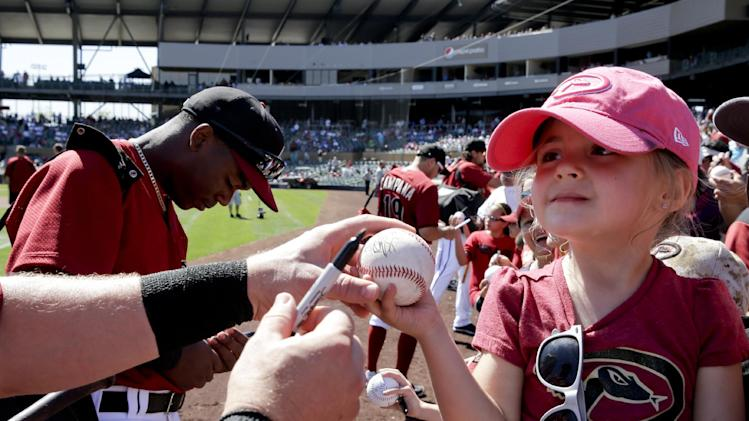 Noelle Scrung, 4, from Gilbert, Ariz. waits for an autograph before an exhibition baseball game between the Arizona Diamondbacks and the Cleveland Indians in Scottsdale, Ariz., Tuesday, March 11, 2014