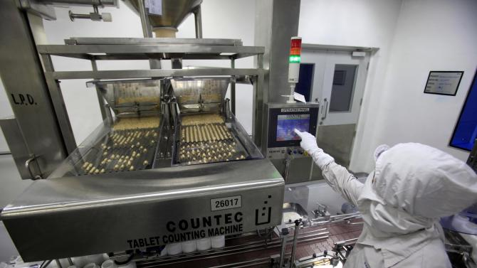 A pharmacist near a tablet counting machine at a Cipla manufacturing unit on the outskirts of Mumbai, India, Thursday, Feb 9, 2012. Efforts by India and the European Union to strengthen trade are threatening India's ability to deliver life-saving medicines to the world's poorest, analysts say as the two sides resume protracted negotiations on a free-trade pact. Health industry workers and activists worry that India may bow to EU demands for strict intellectual property protections and investor guarantees, which could result in the slow poisoning of its own generic pharmaceutical industry. India's $26 billion drug industry has become an immense profit engine, growing at 15-25 percent a year _ but also a lifeline for millions of patients in poor countries, many in Africa, unable to pay sky-high Western prices to treat illnesses that include HIV, malaria, asthma and cancer.  (AP Photo/Rafiq Maqbool)