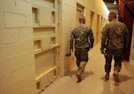 US soldiers walk past prison cells in Bagram prison in 2009. The Afghan government said Tuesday it expected to take full control next week from the United States of the controversial Bagram prison, which numbers Taliban fighters among its 3,000 inmates