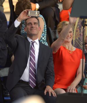 Los Angeles Mayor Eric Garcetti, left, takes a picture of the crowd as his wife Amy Wakeland waves after he was sworn in as mayor of Los Angeles in front of city hall, Sunday, June 30, 2013, in Los Angeles. (AP Photo/Mark J. Terrill)