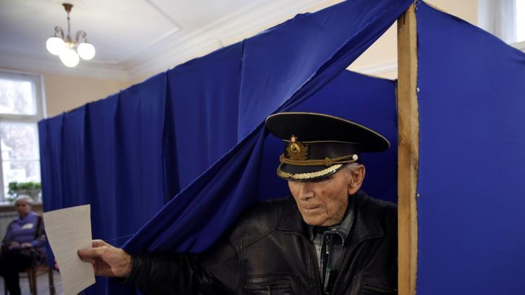 A man leaves a booth to cast his ballot during the referendum on the status of Ukraine's Crimea region at a polling station in Sevastopol