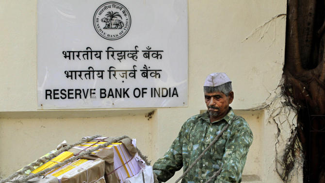 An Indian worker pushes his cart in front of the Reserve Bank of India (RBI) building in Mumbai, India, Tuesday, Jan. 24, 2012. India's central bank said growth will slow to 7 percent this fiscal year, but left interest rates unchanged Tuesday as it struggles to balance a toxic mix of high inflation and a flagging economy. (AP Photo/Rajanish Kakade)