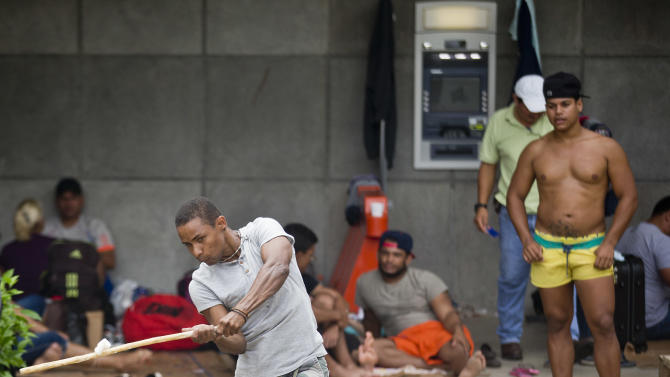 In this Sunday, Nov. 22, 2015 photo, Cuban migrants play baseball outside of the border control building in Penas Blancas, Costa Rica, border with Nicaragua. Cubans interviewed in Costa Rica say that they were making their way from as far south as Chile, Argentina and Brazil. (AP Photo/Esteban Felix)