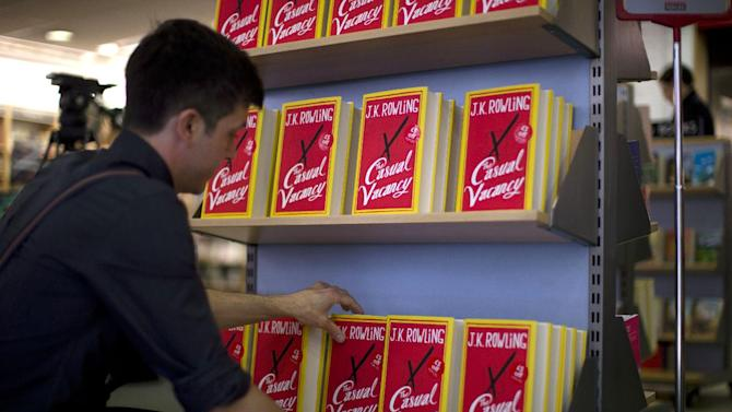 "An employee adjusts copies of  ""The Casual Vacancy"" by author J.K. Rowling at a book store in London, Thursday, Sept. 27, 2012.  British bookshops are opening their doors early as Harry Potter author J.K. Rowling launches her long anticipated first book for adults.  Publishers have tried to keep details of the book under wraps ahead of its launch Thursday, but ""The Casual Vacancy"" has gotten early buzz about references to sex and drugs that might be a tad mature for the youngest ""Potter"" fans.  (AP Photo/Matt Dunham)"