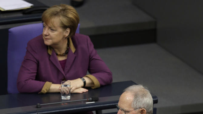 German Finance Minister Wolfgang Schaeuble, front, passes German Chancellor Angela Merkel, rear, after his speech during a meeting of the German federal parliament, Bundestag, in Berlin, Germany, Friday, Nov. 30, 2012. (AP Photo/Michael Sohn)