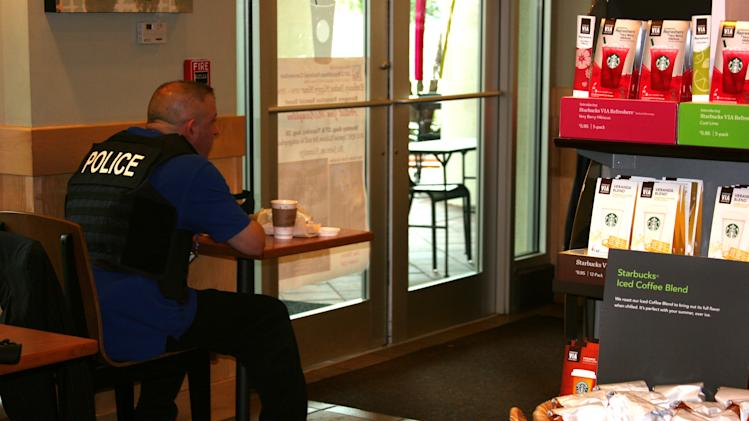 A policeman takes a break at the Starbucks in a hotel near the forum at the Republican National Convention on Monday Aug. 27, 2012. (Torrey AndersonSchoepe/Yahoo! News)