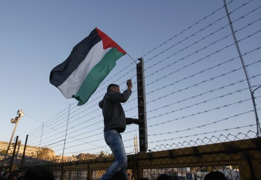 A Palestinian places a flag on a fence outside Ofer prison near Ramallah
