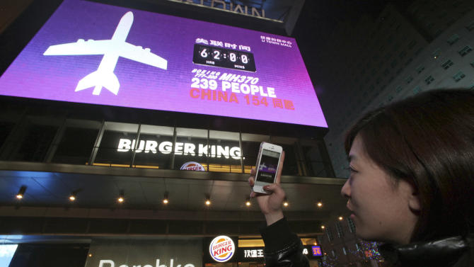 In this photo taken Monday, March 10, 2014, a woman takes a photo of a screen displaying the number of hours since ta Malaysia Airlines passenger jet has gone missing at a mall in Beijing, China. Authorities hunting for the missing Malaysia Airlines jetliner expanded their search on land and sea Tuesday, reflecting the difficulties in locating traces of the plane more than three days after it vanished. (AP Photo) CHINA OUT