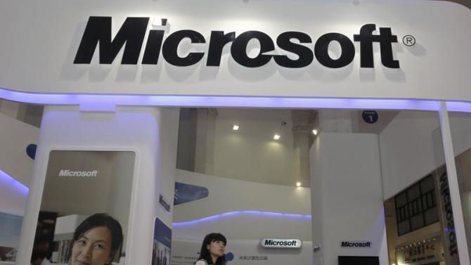 A visitor walks past a Microsoft booth at a computer software expo in Beijing