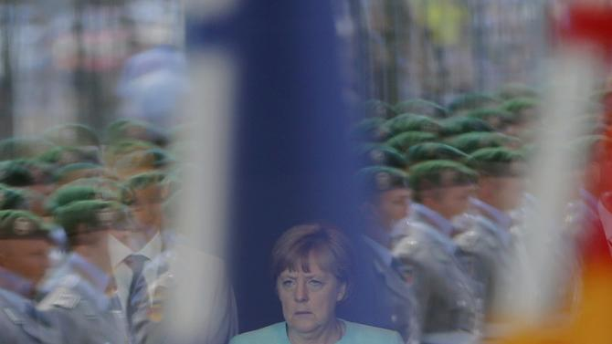 German Chancellor Merkel is reflected in a window as she waits for the arrival of Kosovo's Prime Minister Mustafa at the Chancellery in Berlin
