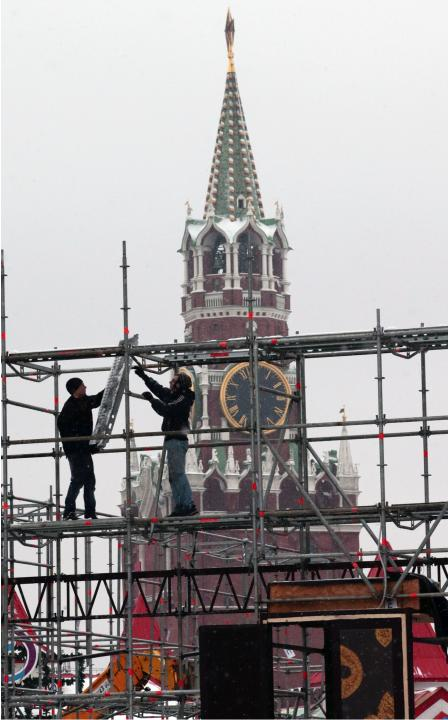 Workers disassemble a Louis Vuitton pavilion which is in the shape of a giant suitcase in central Moscow