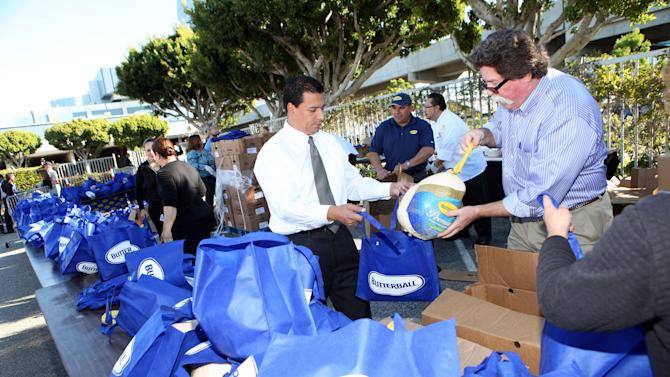 IMAGE DISTRIBUTED FOR BUTTERBALL® - Local volunteers and city council members at the Los Angeles Convention Center hand out 2,000 free turkeys donated by Butterball® and ARAMARK to local families to help make their Thanksgiving Day golden, on Monday, Nov. 19, 2012 in Los Angeles. (Photo by Casey Rodgers/Invision for Butterball®/AP Images)