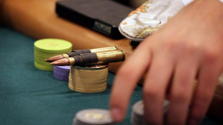 In this photo taken Saturday, Jan. 19, 2013, A player uses bullets as his good luck charm during the MBA Poker Championship and Recruitment Weekend at Planet Hollywood in Las Vegas.(AP Photo/Las Vegas Sun, Leila Navidi)